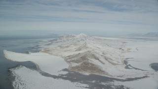 AX125_313 - 6K stock footage aerial video slowly approaching Antelope Island snow mountains in wintertime, Utah
