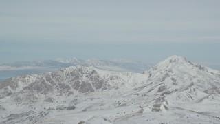 AX125_314 - 6K stock footage aerial video of snowy peaks on Antelope Island in Utah