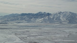 AX125_316 - 6K stock footage aerial video of white snow on the Oquirrh Mountains of Utah in wintertime