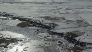 AX125_321 - 6K stock footage aerial video of orbiting small canal near Salt Lake City in winter, Utah