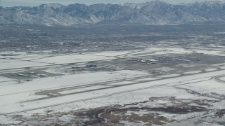 AX125_322 - 6K stock footage aerial video of slow approach to Salt Lake City International Airport with winter snow, Utah