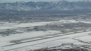 AX125_323 - 6K stock footage aerial video slow approach to SLC International Airport with white winter snow, Utah