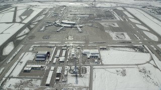 AX125_330 - 6K stock footage aerial video of control tower and terminals at Salt Lake City International Airport with winter snow, Utah