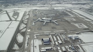 AX125_331 - 6K stock footage aerial video orbit terminals, runways and control tower at SLC Airport with winter snow, Utah