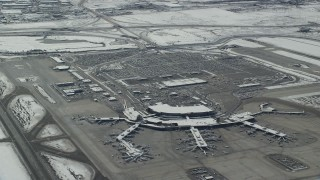 AX125_332 - 6K stock footage aerial video orbit terminals and parking lot at Salt Lake City Airport with winter snow, Utah