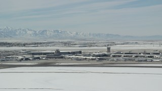 AX125_338 - 6K stock footage aerial video of orbiting the main terminal at Salt Lake City Airport with winter snow, Utah