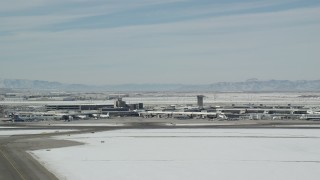 AX125_339 - 6K stock footage aerial video orbit of the main terminal at Salt Lake City Airport with winter snow, Utah