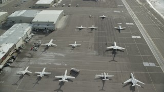 AX126_002 - 6K stock footage aerial video fly over hangars and private planes at Salt Lake City Airport in winter, Utah