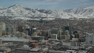 AX126_029 - 6K stock footage aerial video orbit Downtown Salt Lake City and convention center with winter snow, Utah