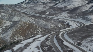 AX126_079 - 6K stock footage aerial video approach bend in freeway through snowy mountain pass in Utah's Wasatch Range