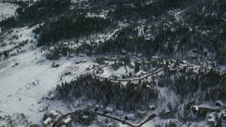AX126_088 - 6K stock footage aerial video orbit upscale homes and evergreen trees covered in winter snow in Park City, Utah