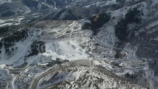 AX126_096 - 6K stock footage aerial video orbit of Utah Olympic Park with winter snow in Park City, Utah