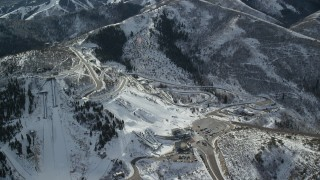 AX126_098 - 6K stock footage aerial video orbit the tracks and ski jumps at Utah Olympic Park with winter snow, Park City
