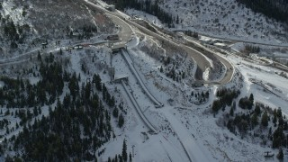 AX126_099 - 6K stock footage aerial video orbiting the ski jumps at Utah Olympic Park with winter snow in Park City