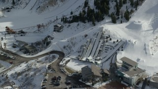 AX126_106 - 6K stock footage aerial video orbit the aerials pool at Utah Olympic Park with winter snow, Park City
