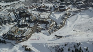 AX126_111 - 6K stock footage aerial video orbit ski slopes, ski lifts and Canyons Resort hotels with winter snow, Park City, Utah