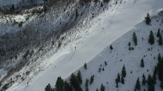 AX126_112 - 6K stock footage aerial video of bird's eye view of skiers on a slope at Canyons Resort in Park City, Utah
