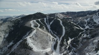 AX126_115 - 6K stock footage aerial video of approaching Canyons Resort ski runs on a snowy Iron Mountain slope, Park City