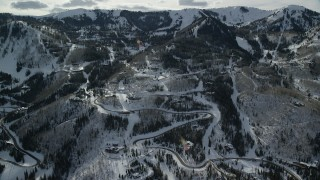 AX126_116 - 6K stock footage aerial video orbiting mountainside mansions with winter snow in Park City, Utah