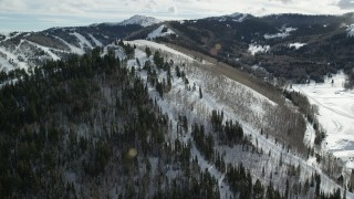 AX126_120 - 6K stock footage aerial video orbit gondolas running up a snowy mountain slope in Park City, Utah