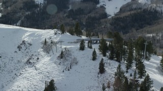 AX126_122 - 6K stock footage aerial video orbiting gondolas on a snowy mountain summit in winter, Park City, Utah