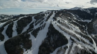 AX126_124 - 6K stock footage aerial video orbit a ski lift and snowy runs at Park City Mountain Resort, Utah
