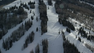 AX126_125 - 6K stock footage aerial video orbit ski lift and skiers at Park City Mountain Resort in winter, Utah