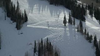 AX126_126 - 6K stock footage aerial video orbit skiers on a run at Park City Mountain Resort in winter, Utah