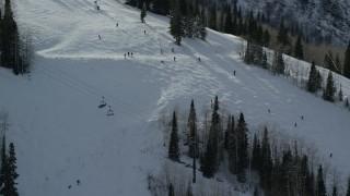 AX126_127 - 6K stock footage aerial video orbit skiers on a snowy slope at Park City Mountain Resort in wintertime, Utah