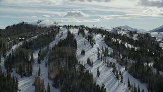 AX126_132 - 6K stock footage aerial video orbit ski lifts and slopes at Deer Valley Ski Resort with winter snow, Utah