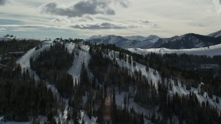 AX126_133 - 6K stock footage aerial video orbit snowy mountains with ski runs and lifts at Deer Valley in winter, Utah
