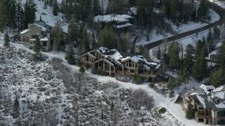 AX126_138 - 6K stock footage aerial video orbit Deer Valley mansion with winter snow in Utah