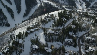 AX126_144 - 6K stock footage aerial video orbit and reverse from mansions on snowy mountain, Deer Valley, Utah, winter