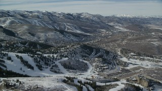 AX126_146 - 6K stock footage aerial video orbit hilltop homes near the small town of Park City with winter snow, Utah