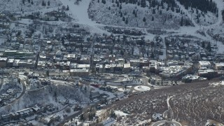 AX126_149 - 6K stock footage aerial video orbit small town in the shadow of a snowy mountain in winter, Park City, Utah