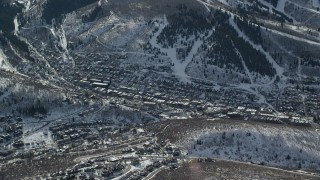 AX126_150 - 6K stock footage aerial video orbit small town in winter shaded by snowy mountain, Park City, Utah