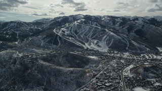 AX126_151 - 6K stock footage aerial video of ski runs on a snowy mountain slope overlooking small town in winter, Park City, Utah