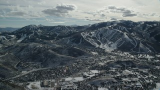 AX126_153 - 6K stock footage aerial video orbiting the small town of Park City in winter, Utah