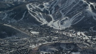 AX126_154 - 6K stock footage aerial video of snowy ski runs beside a small town in winter, Park City, Utah