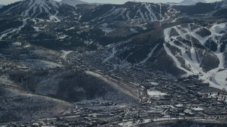 AX126_156 - 6K stock footage aerial video orbit small mountain town at the base of snowy peak in winter, Park City, Utah
