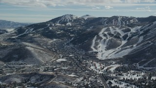 AX126_159 - 6K stock footage aerial video orbit small town between snowy hills and mountains in winter, Park City, Utah