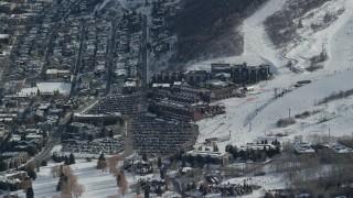AX126_162 - 6K stock footage aerial video orbit ski resort hotels at the base of snowy runs in winter, Park City, Utah