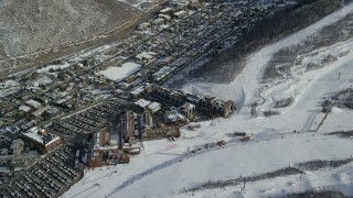 AX126_165 - 6K aerial stock footage video of ski resort hotels at the bottom of a ski run in winter, Park City, Utah