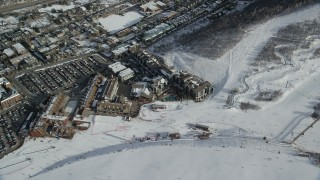 AX126_166 - 6K stock footage aerial video orbiting hotels at Park City Mountain Resort with skiers and winter snow, Utah