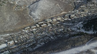 AX126_167 - 6K stock footage aerial video of flying by the small mountain town of Park City in wintertime, Utah