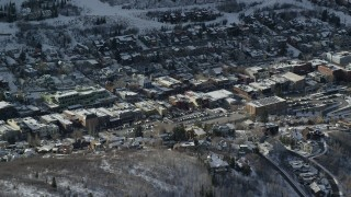 AX126_175 - 6K stock footage aerial video orbit shops in Park City's town center with winter snow, Utah