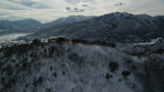 AX126_198 - 6K stock footage aerial video approach and fly over snowy Wasatch Range mountain in winter to reveal Midway, Utah
