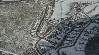 AX126_205 - 6K stock footage aerial video orbit snowy neighborhood with tract homes in wintertime, Midway, Utah