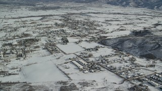 AX126_206 - 6K stock footage aerial video orbit small town homes covered in winter snow, Midway, Utah
