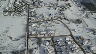 AX126_207 - 6K stock footage aerial video fly over small residential neighborhood with snowy rooftops in winter, Midway, Utah
